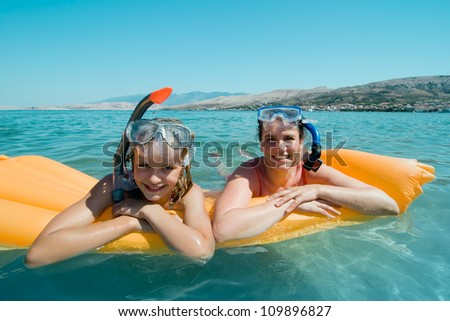 Mother and daughter lying on air mattress in sea water - stock photo
