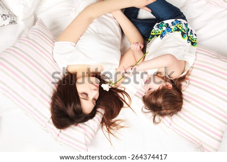 mother and daughter lying on the bed with flower - stock photo