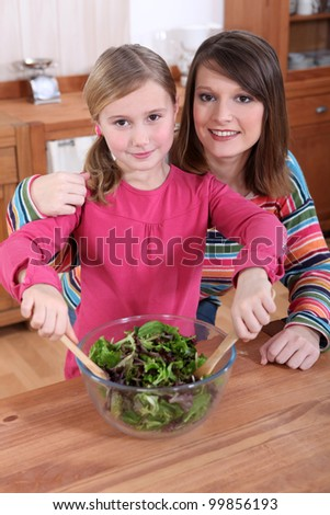 Mother and daughter making a salad together - stock photo
