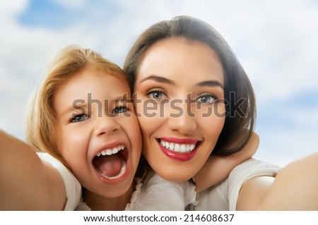 mother and daughter making a selfie - stock photo