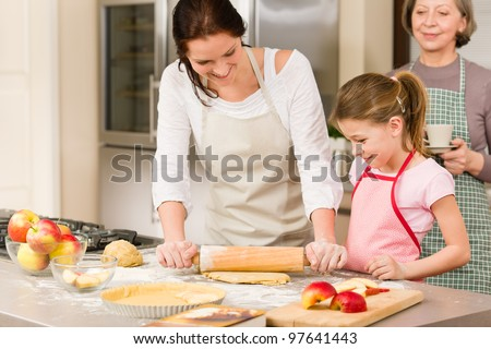 Mother and daughter making apple pie together grandmother check recipe - stock photo