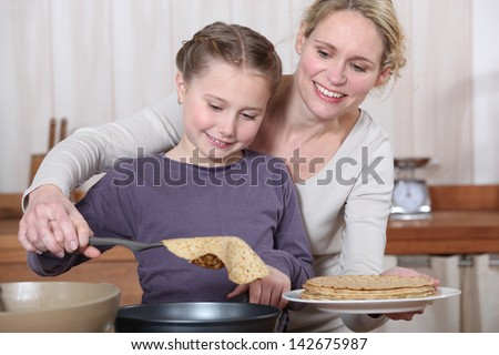 Mother and daughter making crepes together - stock photo