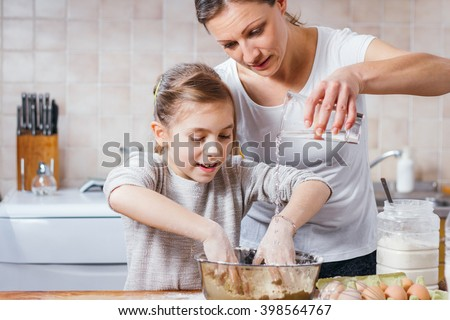 Mother and daughter making dough - stock photo