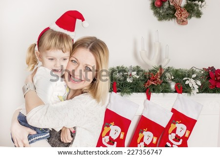 mother and daughter near Christmas tree laughing - stock photo