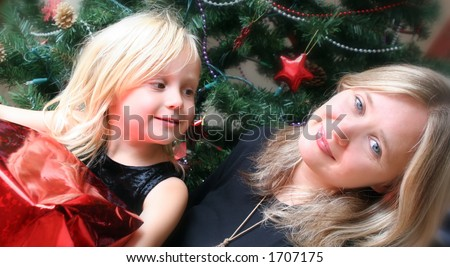 Mother and daughter next to christmas tree - stock photo