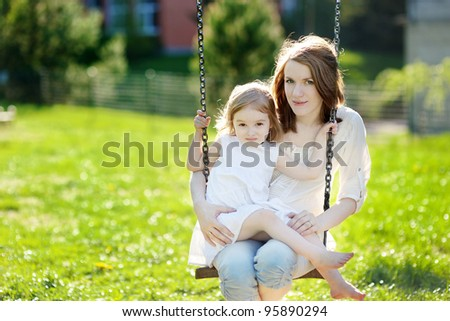 Mother and daughter on a garden swing - stock photo
