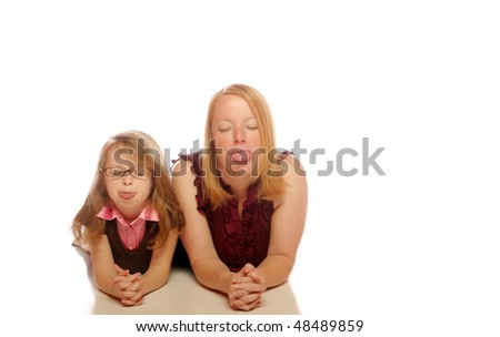 Mother and daughter on an isolated background sticking their tongues out - stock photo
