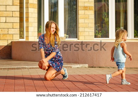 Mother and daughter on the walk in the city park. The child runs away from his mother. - stock photo