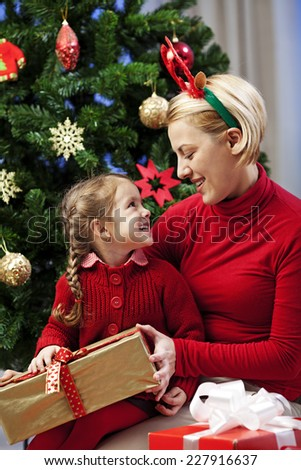 Mother and daughter opening christmas presents on christmas eve  - stock photo
