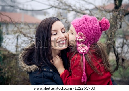 Mother and daughter outside in cold weather - stock photo
