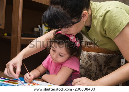 Mother and daughter paint a picture - stock photo