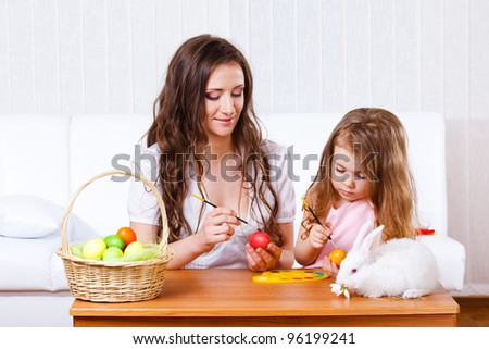 Mother and daughter painting Easter eggs - stock photo