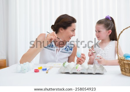 Mother and daughter painting easter eggs at home in the living room - stock photo