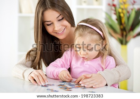 Mother and daughter playing at home. They assembling Jigsaw Puzzle. - stock photo