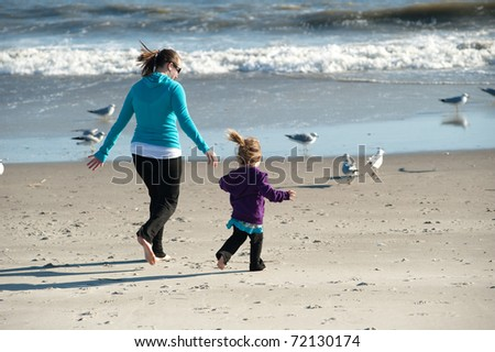 mother and daughter playing at the beach - stock photo