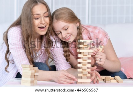 mother and daughter   playing board game - stock photo