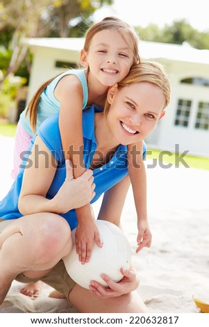 Mother And Daughter Playing Game Of Volleyball In Garden - stock photo