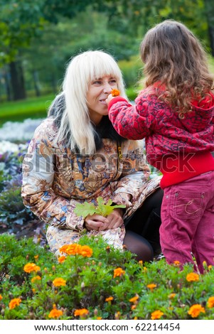 Mother and daughter playing in a park - stock photo