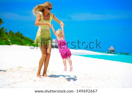 Mother and daughter playing on the white sandy beach at Maldives - stock photo