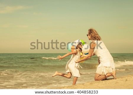 Mother and daughter playing with balloons on the beach at the day time. Concept of friendly family. - stock photo