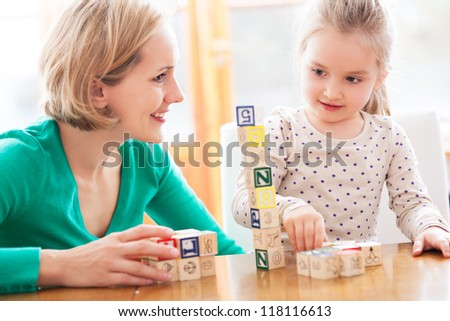 Mother and daughter playing with blocks - stock photo