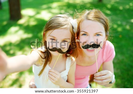 Mother and daughter playing with paper moustaches on a stick and other party accessories - stock photo