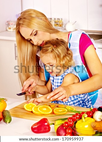 Mother and daughter prepare at kitchen. - stock photo