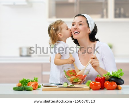 mother and daughter prepare salads - stock photo