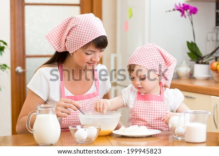 Mother and daughter preparing cookies together at kitchen - stock photo