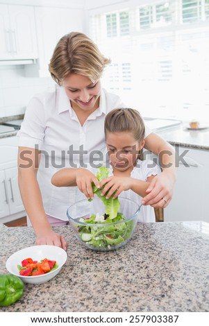 Mother and daughter preparing salad at home in kitchen - stock photo