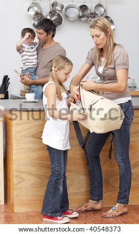 Mother and daughter preparing the bag for school in the kitchen - stock photo