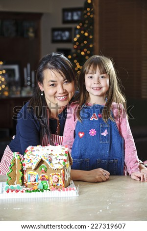 mother and daughter / proud of their christmas project / a gingerbread house - stock photo