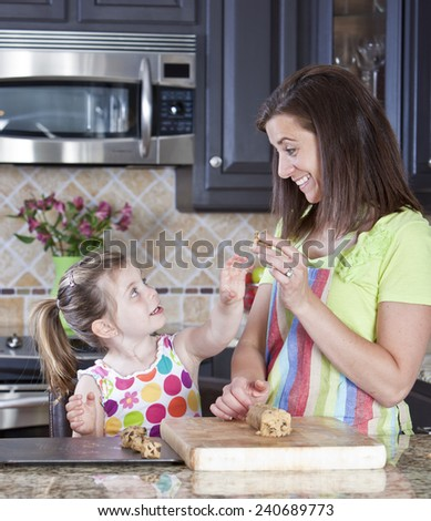 Mother and daughter putting cookie dough onto baking sheet in kitchen  - stock photo