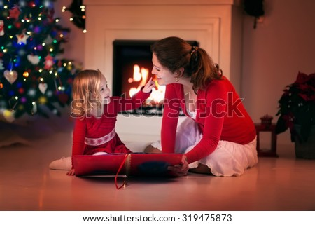 Mother and daughter read a book at fireplace on Christmas eve. Family with child celebrating Xmas. Decorated living room with tree, fire place and candles. Winter evening at home for parents and kids. - stock photo