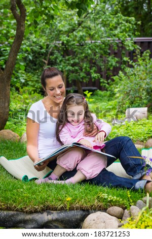 Mother and daughter read book outdoors - stock photo