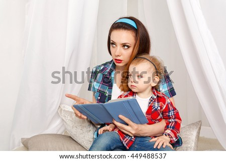 Mother and daughter read the e-book. Fairy tales. Mother explains All Read. Young mother and baby daughter hugging. Girls dressed in plaid shirt. Family education - stock photo