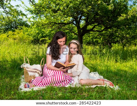 Mother and daughter reading a book in the park. Family time - stock photo