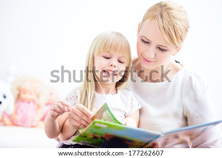 Mother and daughter reading a colorful book at home - stock photo