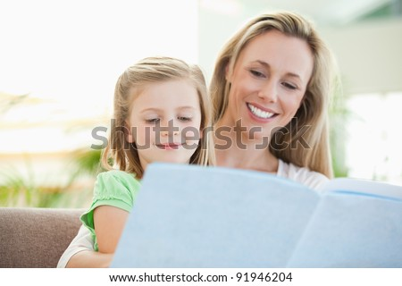 Mother and daughter reading a magazine together on the couch - stock photo