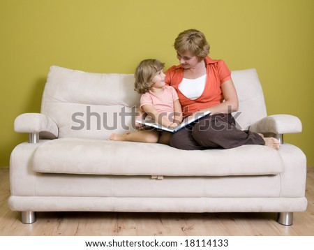 Mother and daughter reading book on sofa - stock photo
