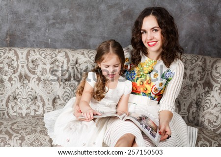Mother and daughter reading together on the couch - stock photo