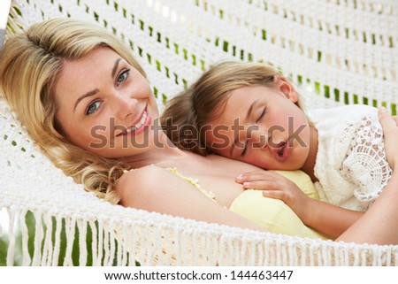 Mother And Daughter Relaxing In Beach Hammock - stock photo