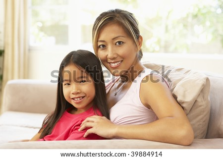 Mother And Daughter Relaxing On Sofa At Home - stock photo