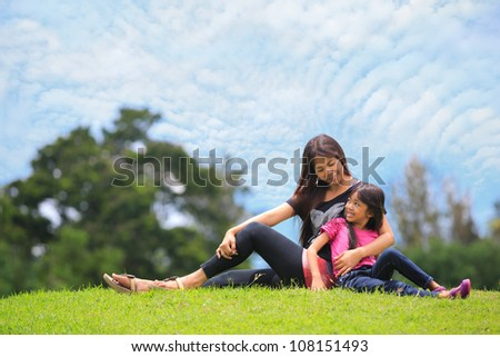 Mother and daughter relaxing sitting grass - stock photo