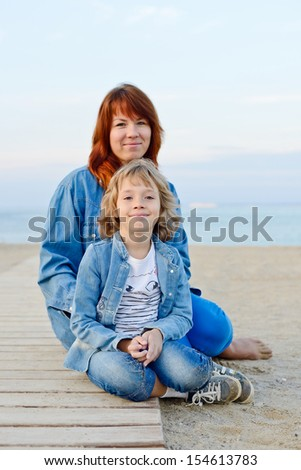 mother and daughter resting near the sea - stock photo