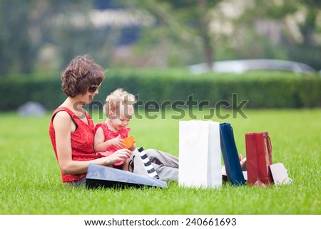 Mother and daughter resting on the lawn after shopping - stock photo