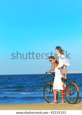 mother and daughter riding a bike  on the beach - stock photo