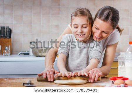Mother and daughter rolling dough with rolling pin - stock photo