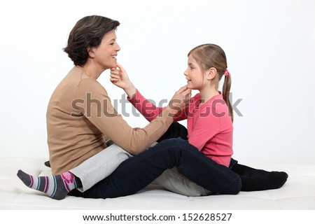 Mother and daughter sat facing each other - stock photo