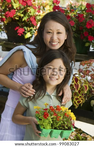 Mother and Daughter Selecting Plants - stock photo